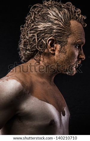 man covered in mud, naked, in profile - stock photo