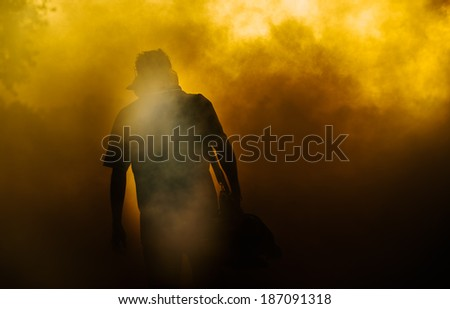 Man covered with smoke while fogging into the drain to prevent spread of dengue fever - stock photo