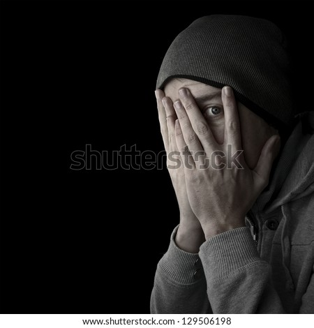 man covering face looking through fingers black background with copy space - stock photo