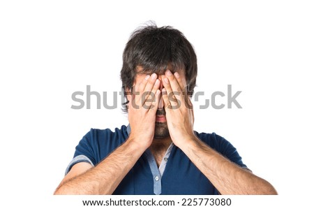 Man covering his eyes over isolated white background