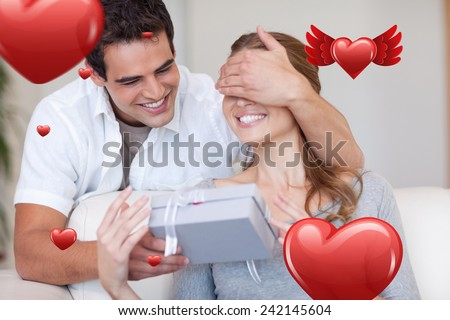 Man covering the eyes of his girlfriend while giving her a present against love heart pattern - stock photo