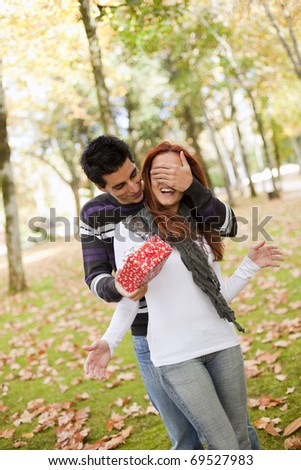 man covering the eyes to her girlfriend giving her a present (selective focus with shallow DOF)