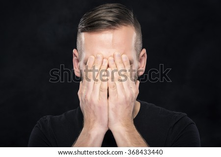 Man covers face with hands on dark background. - stock photo
