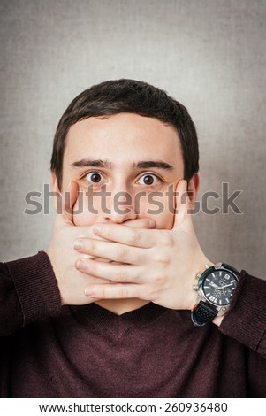 man covers his mouth with his hands, fear, does not want to roar, laughing - stock photo