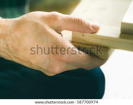 Man crafting wooden chair object keeping wooden boards in hands. Do it yourself project making process closeup