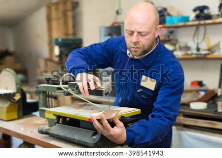 Man craftsman working with unfinished guitar indoors