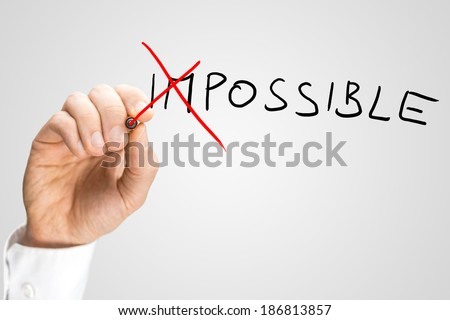 Man crossing through the Im in the handwritten word Impossible on a virtual screen with a red marker pen in a concept of opposites for Impossible - Possible.