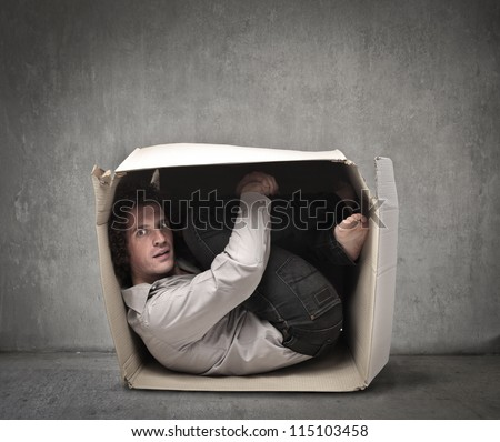 Man crouched in a box - stock photo