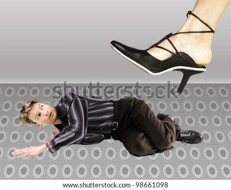 man crouching under the girl's feet - stock photo