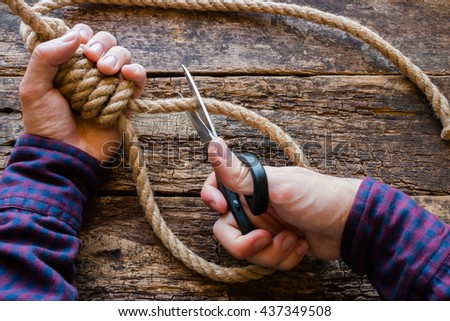 man cut the rope with a slipknot concept stop suicide - stock photo