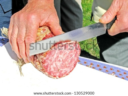 man cuts a slice of salami with a knife