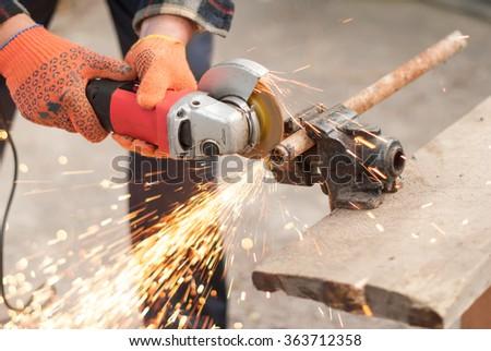 Man cuts pipe power saw. - stock photo