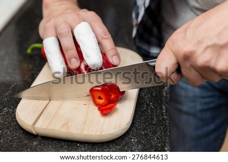 Man cuts with injured fingers red peppers