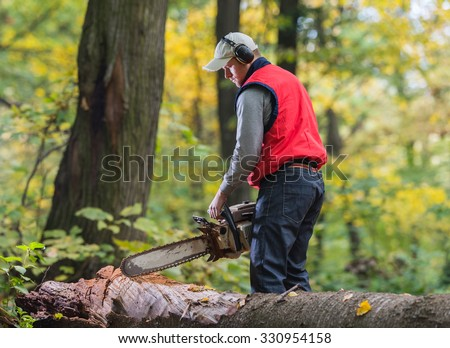 Man cutting a branch with chainsaw - stock photo