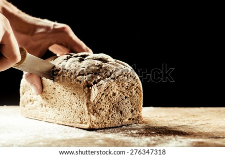 Man cutting a freshly baked crusty homemade loaf of wholegrain bread with a knife on a wooden cutting board with copyspace on a dark background - stock photo