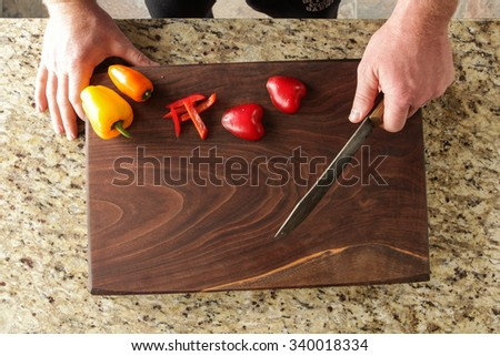 Man cutting bell peppers on a beautiful cutting board in the kitchen - stock photo