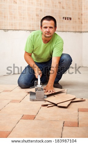 Man cutting ceramic floor tiles - looking in the camera - stock photo