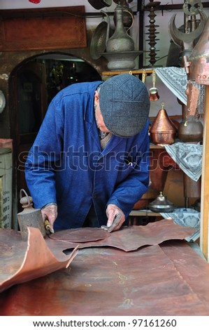 man cutting copper plaque (sheet) - stock photo
