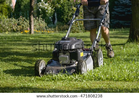 Man cutting grass by lawn mower, powerful petrol lawn mower in sunlight