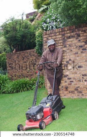 Man cutting grass in a garden yard with lawn mower  - stock photo