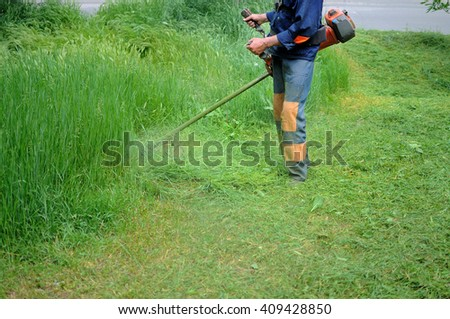 Man cutting grass in garden with the lawn trimmers - stock photo