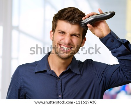 Man Cutting His Hair With Razor, Indoor - stock photo