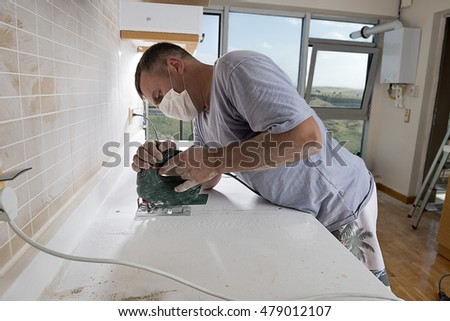 Man cutting kitchen countertop using electric jig saw with space for ...