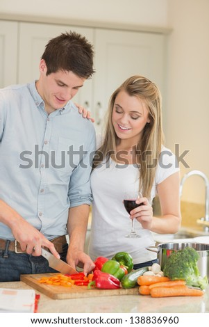 Man cutting peppers with woman drinking wine in kitchen - stock photo