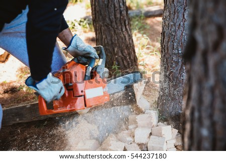 Man cutting some piece of wood by chainsaw