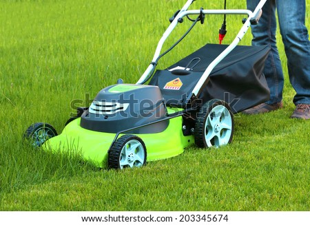 Man cutting the grass with electric lawn mower  - stock photo