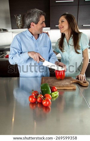man cutting the vegetable con his husband looking him - stock photo
