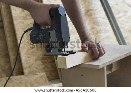 Man cutting wood block with fretsaw at the workshop