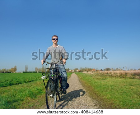 Man cycling in early spring among green fields in the countryside