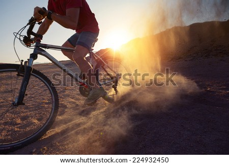 Man cycling in the desert with lot of dust - stock photo