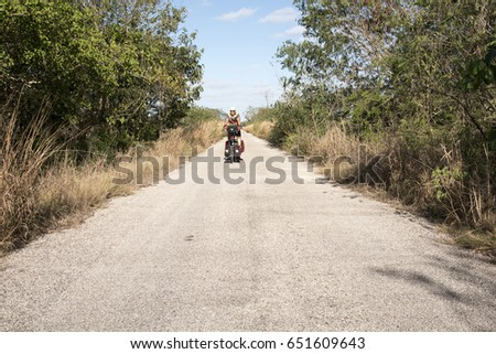 Man cycling on a folding bike in secondary road,Mexico