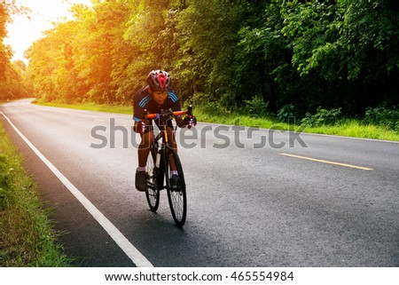 Man cycling on the road morning sunrise