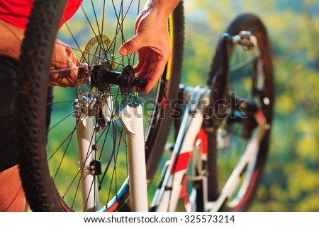 Man cyclist repairing a bike  against the background of blue sky at afternoon - stock photo