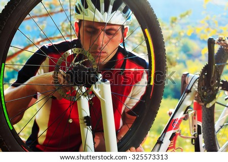 Man cyclist repairing a bike  against the background of blue sky at afternoon