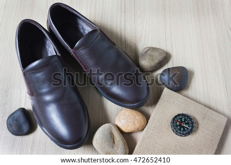 Man dark burnt brown leather shoes with note book or diary with compass
