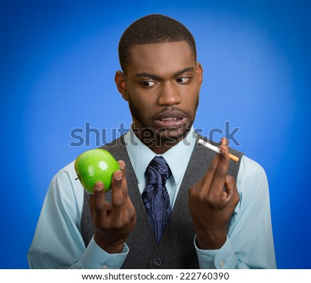 Man decides to quit smoking. Stressed businessman and healthy life choices, craving cigarette versus green apple isolated on blue background. Face expression body language bad hazardous human habits - stock photo