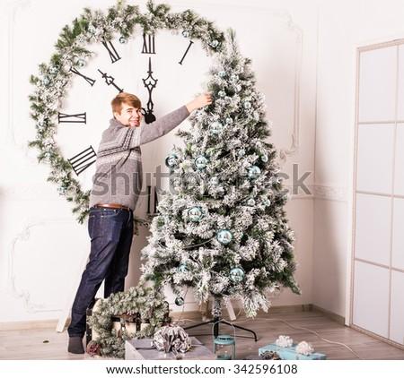 man decorating Christmas tree  - stock photo