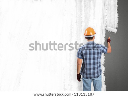 man decorating or painting house with a paint brush