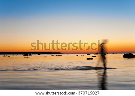 Man defocused silhouettes walking in sea water at multicolored sunset background. Long exposure. Outdoors vibrant horizontal image.