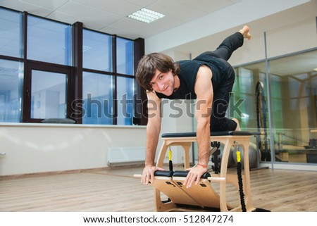 Man demonstrating pilates exercise on balance. Man shows how to use pilates equipment