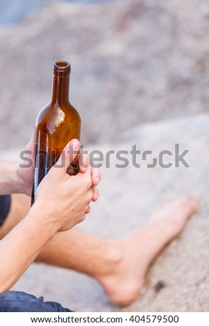 Man depressed holding wine bottle sitting on sea shore outdoor. People abuse and alcoholism problems - stock photo