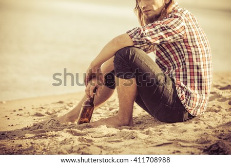 Man depressed with wine bottle sitting on beach outdoor. People abuse and alcoholism problems - stock photo