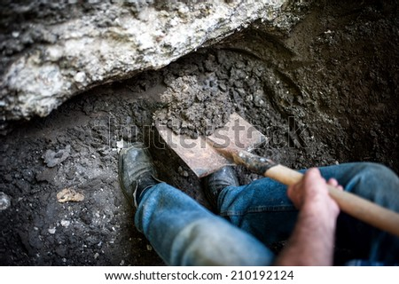 man digging a hole in the ground with shovel and spade - stock photo