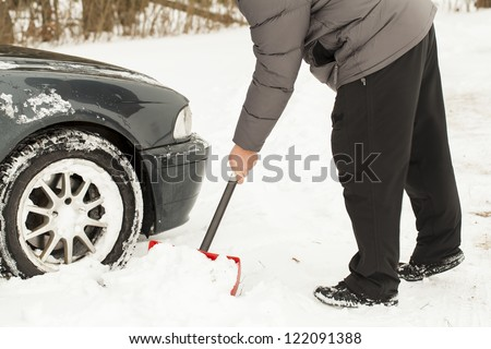 Man digging car out of the snow - stock photo