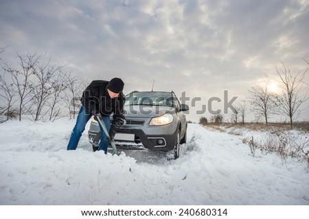 man digging up stuck in snow car - stock photo