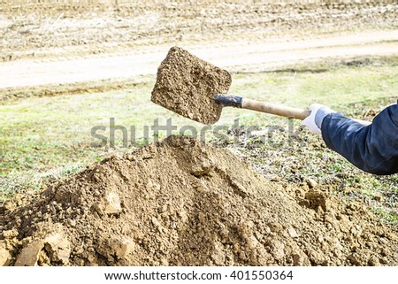 man digs a pit, shovel for digging the ground, digging the garden, a lot of sand, gardener and cultivation of land, digging a hole, the beginning of the gardening season - stock photo
